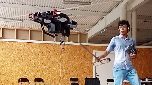 Man poking hovering drone with a stick